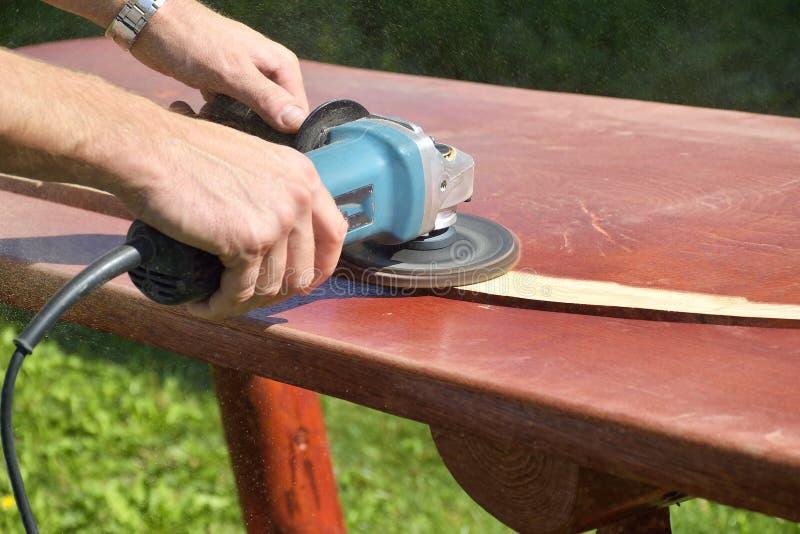 Närbilden av snickare` s räcker arbete med den elektriska slipmaskinen - polerande gammal färg från trätabellen fotografering för bildbyråer