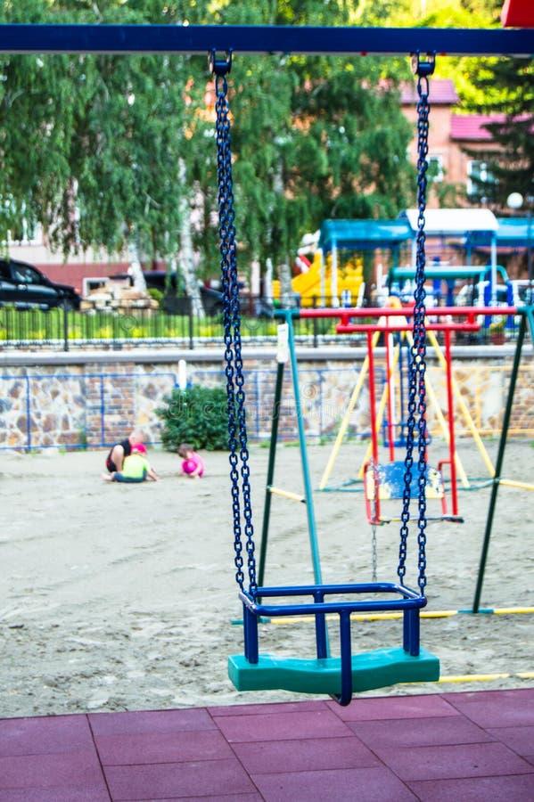Närbilden av tom färgrik plast- behandla som ett barn gunga på lekplats i parkerar på sommardag arkivbild