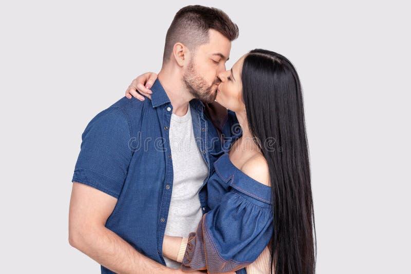 Närbilden av unga romantiska par är kyssa och tycka om företaget av de isolerade bärande grov bomullstvillkläder på ashy-grå färg royaltyfri bild
