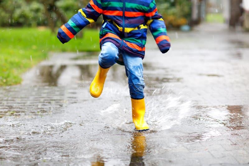 Närbilden av ungen som bär gula regnkängor och går under, regnar snöslask, regnar och snöar på kall dag fotografering för bildbyråer