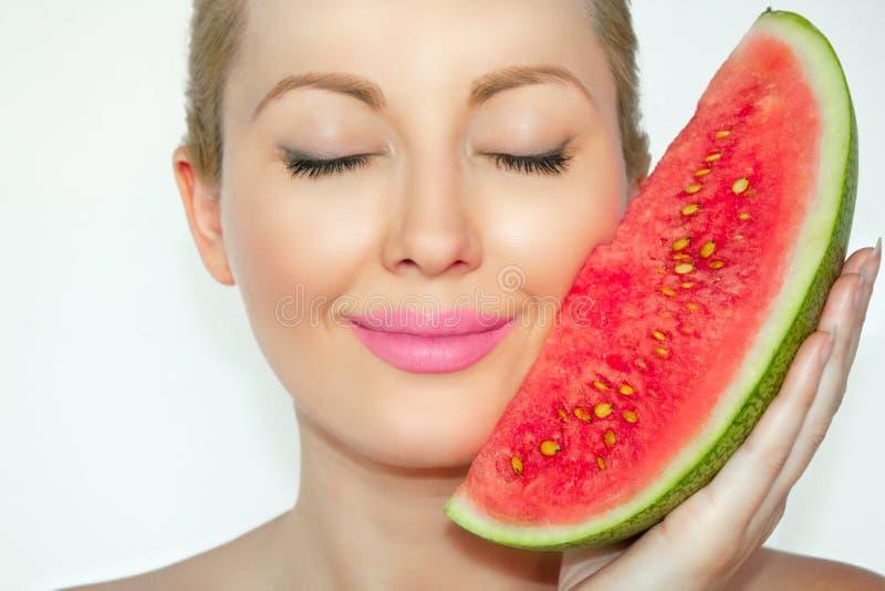 Närbilden den härliga unga kvinnan som rymmer en vattenmelonframsida, synar stängt och artigt leende royaltyfri fotografi
