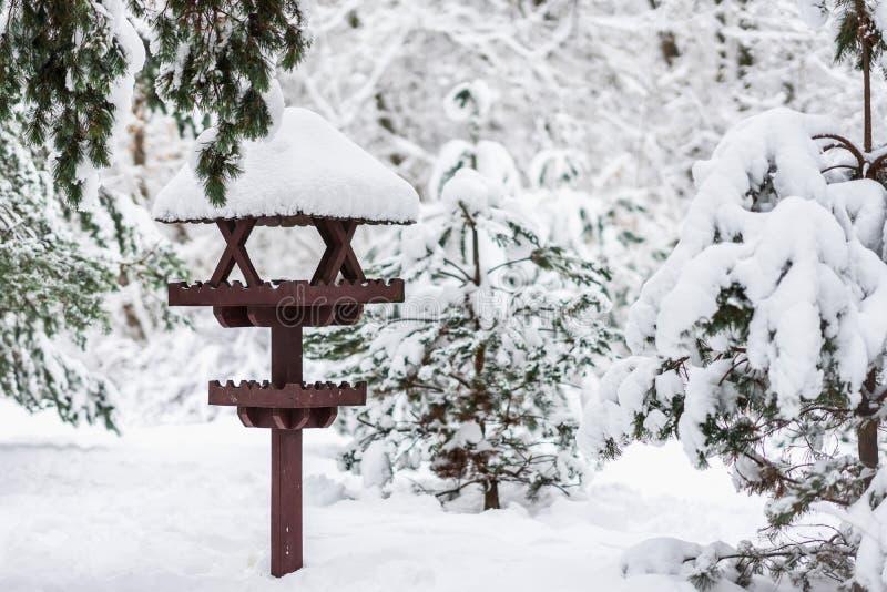 Närbilden för vinterparkerar den träfågelförlagemataren som täckas med snö, vinterdag in arkivbilder