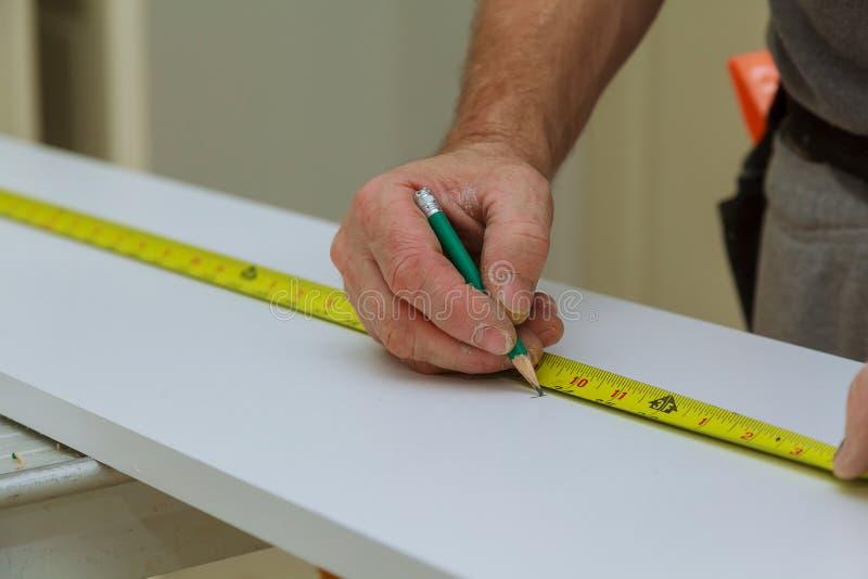 Närbilden mannen mäter ett träbräde med en linjal och markerar med blyertspennan royaltyfria foton