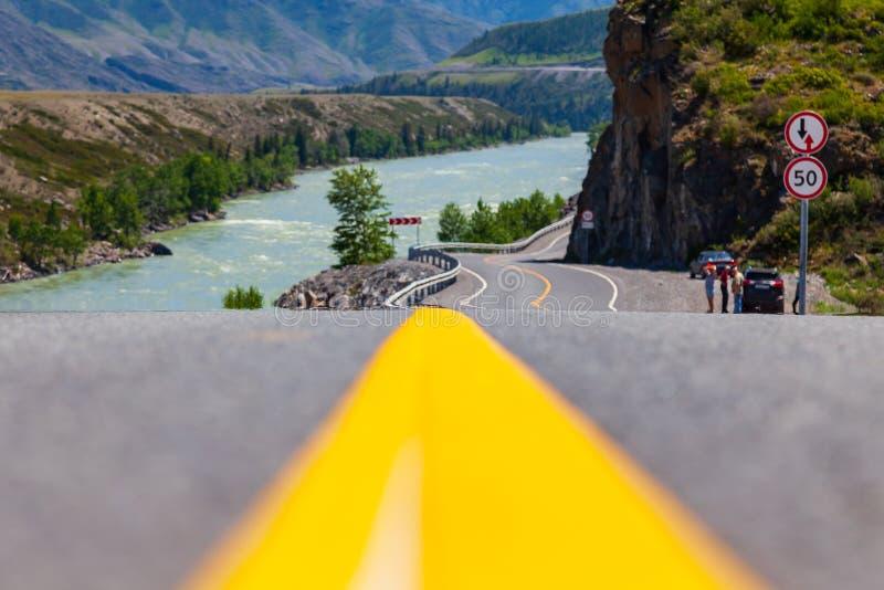 Närbilden på en gul delande remsa på en asfaltväg som sträcker in i de Altai bergen nära, vaggar med vaggar och en flod med fotografering för bildbyråer