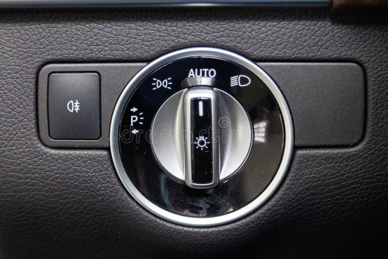 Närbilden på knapparna för billyktaströmbrytarekontroll och automatiska justerar nivåinstrumentbrädan i bil i baksidan av en suv, arkivfoto