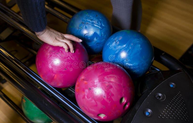 Närbilden på tonåriga barn räcker att rymma bowlingklot mot bowlingbanan - bild Gladlynta ungar är klara att spela - bild _ fotografering för bildbyråer
