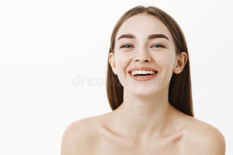 Närbilden sköt av den härliga och lyckliga unga charmiga flickvännen som poserar naket skratta och le stirra på kameran som om arkivbilder