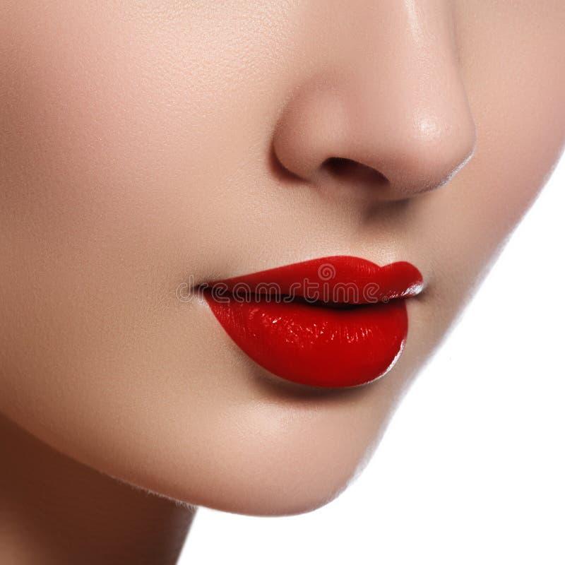 Närbilden sköt av kvinnakanter med glansig röd läppstift Rött kantsmink för glamour, renhethud Retro skönhetstil härlig modell royaltyfria foton