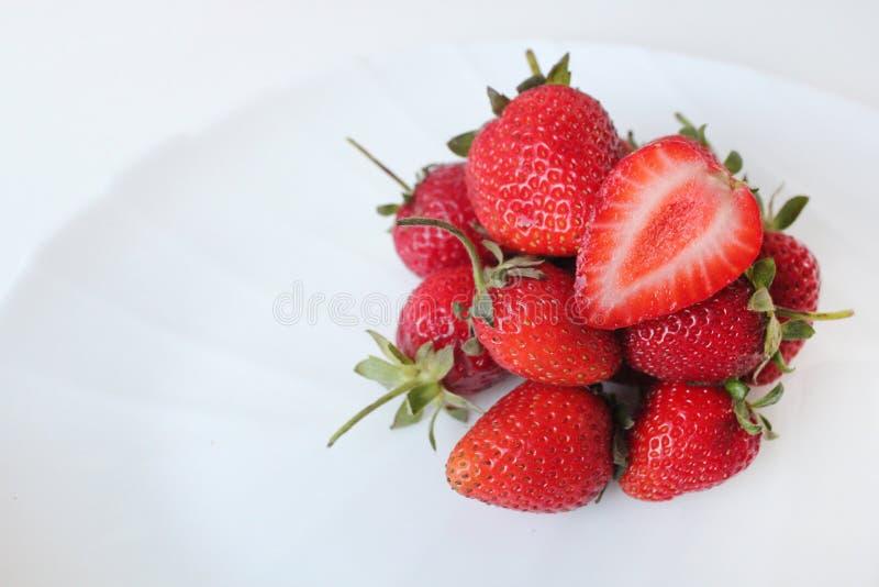 Närbilden sköt av nya jordgubbar på en vit platta bakgrund isolerad white royaltyfria foton