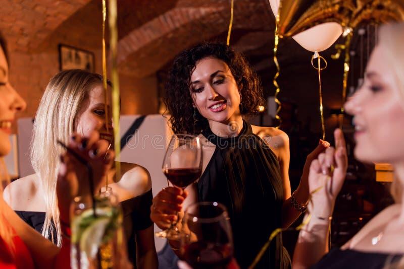 Närbilden sköt av positiva härliga kvinnliga vänner som lyfter exponeringsglas av vin till sammanträde för den lyckliga händelsen arkivfoto