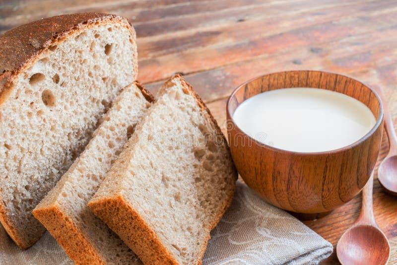 Närbilden skivade bröd, och en träkopp av mjölkar på diagonalt gammalt royaltyfria bilder