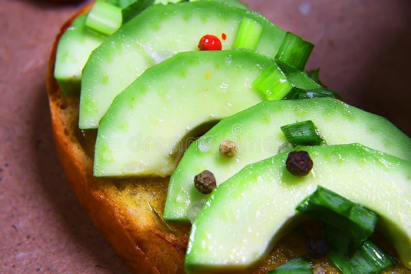 Närbilden skjuter in, bruschettaen med den skivade avokadot, begreppet av sunt äta, kopieringsutrymme, uppsättning för bästa sikt royaltyfria foton