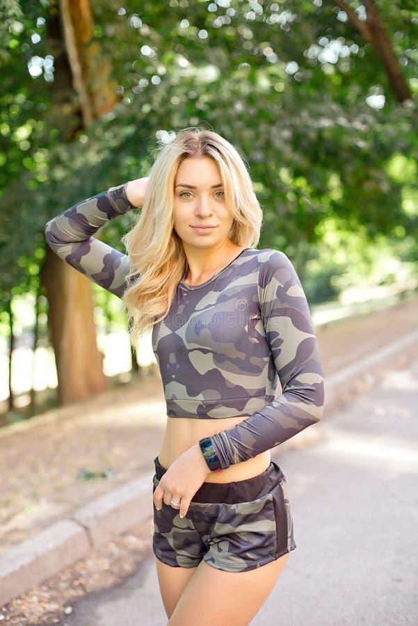 Närbilden som skjutas av den färdiga unga kvinnan som utomhus står i, parkerar Muskulös ung kvinna i militärt se för sportswear royaltyfri fotografi