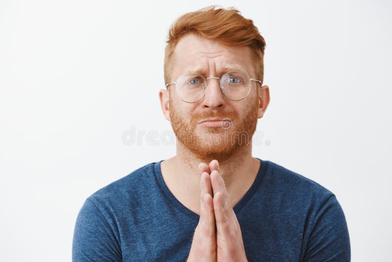 Närbilden som skjutas av rödhårig manman i behov som står med händer ber in, över bröstkorg och att snörpa kanter och rynka panna fotografering för bildbyråer