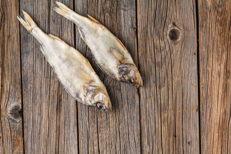 Närbilden torkade fisken på en mörk träbakgrund royaltyfria foton