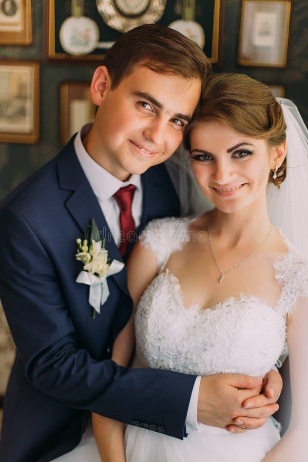 Närbildfamiljfoto av bruden och brudgummen som poserar i restaurang med tappninginre royaltyfria foton