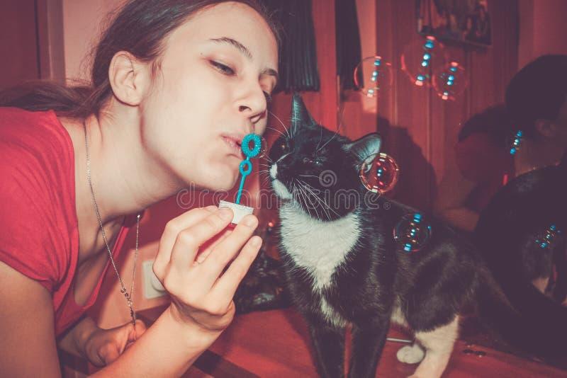 Närbildflicka som blåser såpbubblor och den nyfikna svartvita katten som intresseras i dem arkivfoto