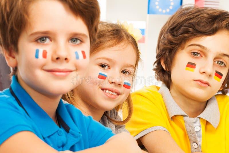 Närbildfoto av barn med flaggor på kinder arkivfoto