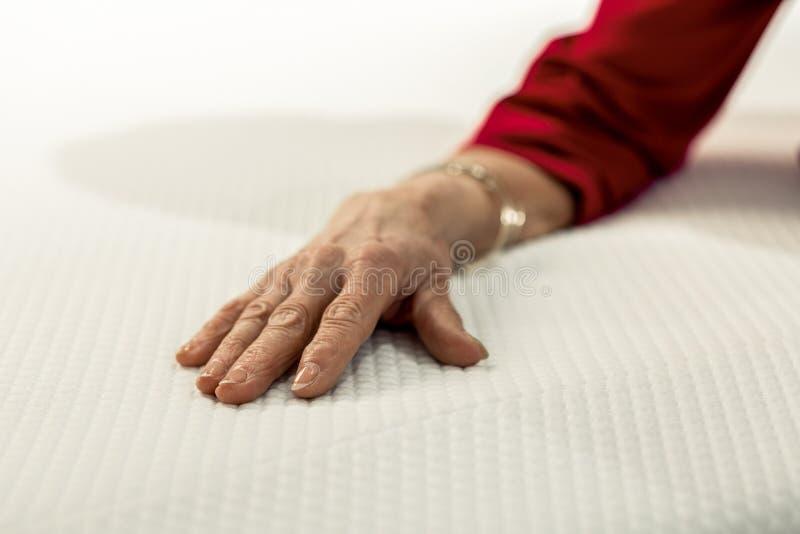 Närbildfoto av den äldre kvinnahanden på sängtorkdukarna fotografering för bildbyråer