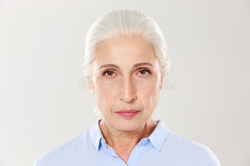 Närbildfoto av den allvarliga äldre kvinnan som ser kameran fotografering för bildbyråer