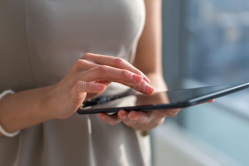 Närbildfoto av en affärskvinna med den digitala minnestavlan i händer Kvinnlign räcker maskinskrivning, att smsa och messaging, g arkivbild