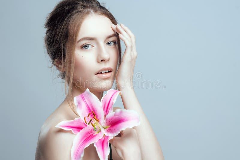 Närbildfoto av en härlig flicka med en liljablomma Hon har rent och flår även, ganska hår royaltyfri fotografi