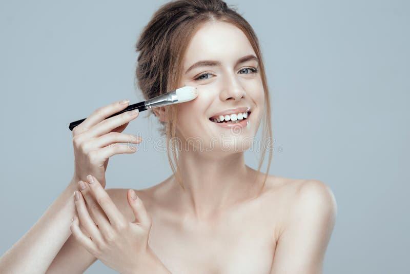 Närbildfoto av en härlig flicka med en sminkborste Hon har rent och flår även, ganska hår arkivfoto