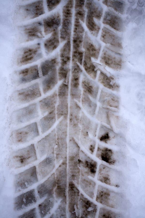 Närbildfoto av en väg i vintersäsongen På den smutsiga snön är ett beskyddande synligt från gummihjulen av lastbilen arkivbild