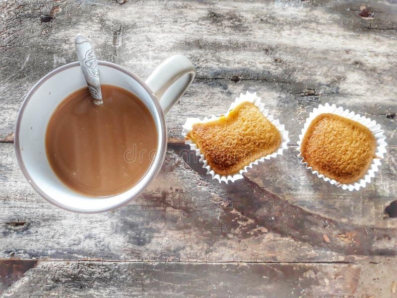 Närbildfoto av kaffe och bröd för espresso som varmt bakas på en träbakgrund Top besk?dar arkivfoton