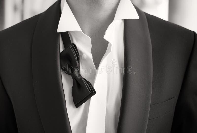 Närbildfoto av mannen i smoking med den öppna skjortan och den lösa flugan arkivfoto