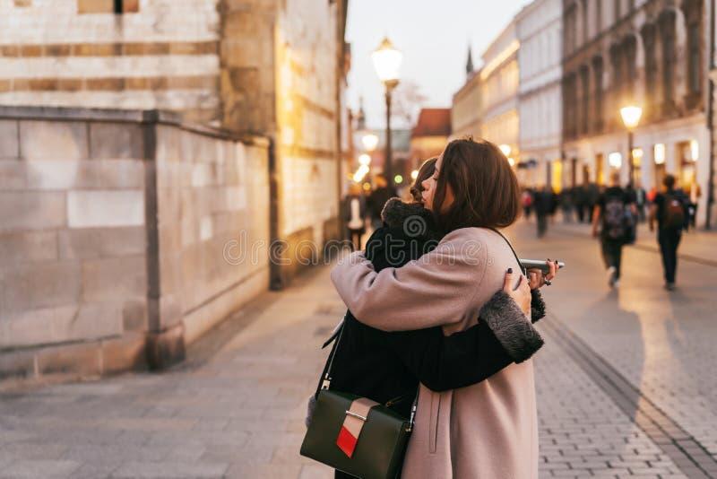 Närbildfoto av två emotionella kvinnavänner som kramar sig royaltyfri fotografi