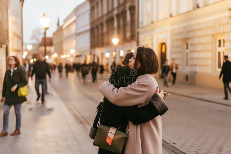 Närbildfoto av två emotionella kvinnavänner som kramar sig arkivfoto