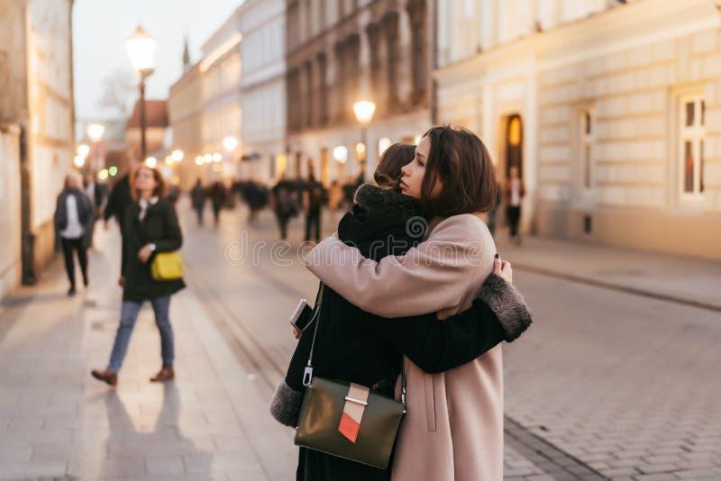 Närbildfoto av två emotionella kvinnavänner som kramar sig arkivbilder