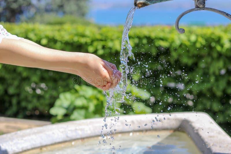 Närbildfoto av ung flickatvagninghänder i stadsspringbrunn med vatten som plaskar på dem med många droppar royaltyfria foton
