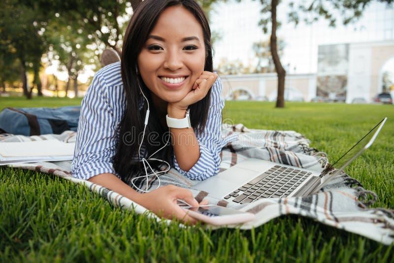 Närbildfoto av ung le asiatisk kvinnlig student lyssnande t royaltyfri foto