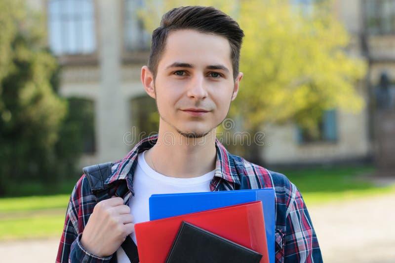 Närbildfotostående av den stiliga ärliga vänliga grabben som rymmer flera notepads i händer som framme står av universitetsområde arkivfoton