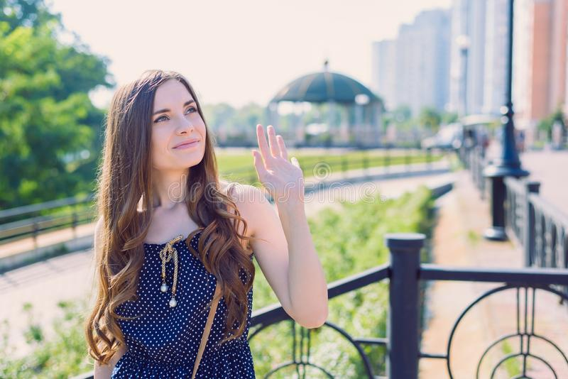 Närbildfotoståenden av sött charma med trevligt vinka för frisyrdam gömma i handflatan till flickvänanseendet nära räcke som upp  royaltyfria bilder