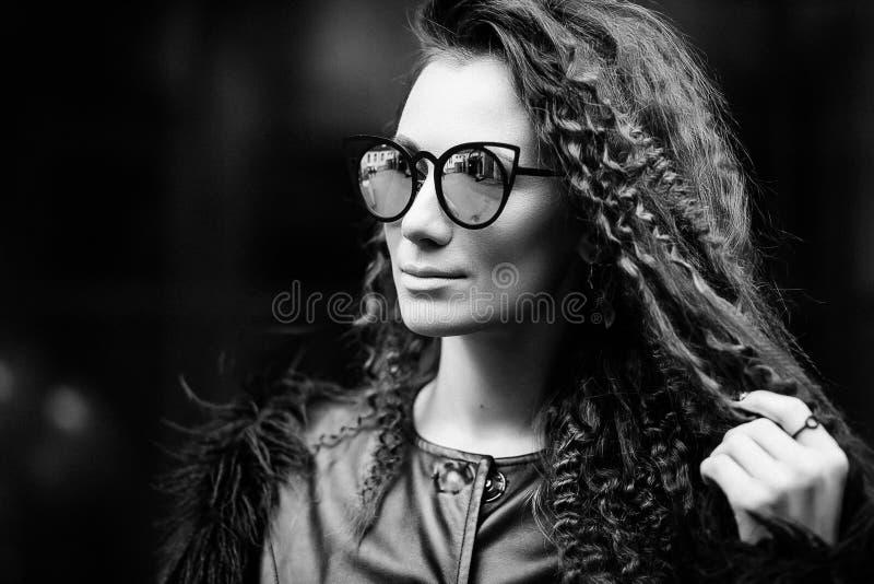 Närbildframsidastående av den unga härliga kvinnan med perfekt hud i solglasögon för öga för katt` s i cityscapen Härlig le flick fotografering för bildbyråer