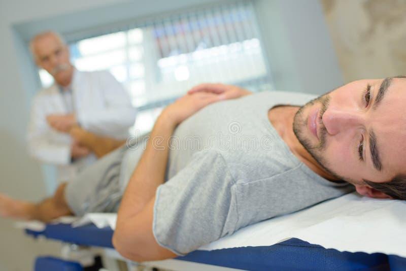 Närbildfysioterapeut som sträcker det unga patientbenet royaltyfri foto