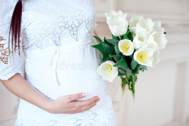 Närbildgravid kvinna i vitt rum arkivbilder