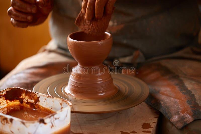 Närbildhänder av en manlig keramiker i förklädeformer bowlar från lera, selektiv fokus royaltyfri foto