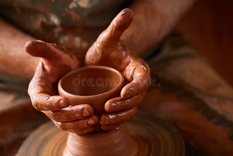 Närbildhänder av en manlig keramiker i förklädeformer bowlar från lera, selektiv fokus fotografering för bildbyråer