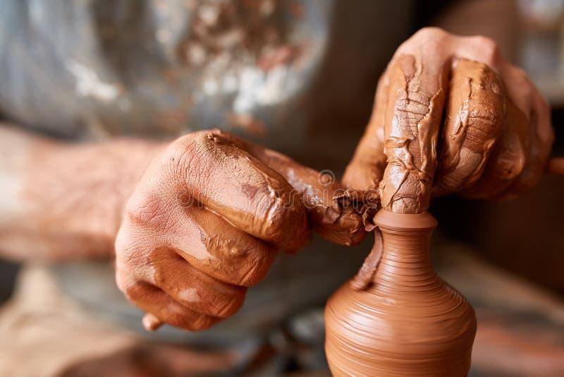Närbildhänder av en manlig keramiker i förklädeformer bowlar från lera, selektiv fokus royaltyfri fotografi