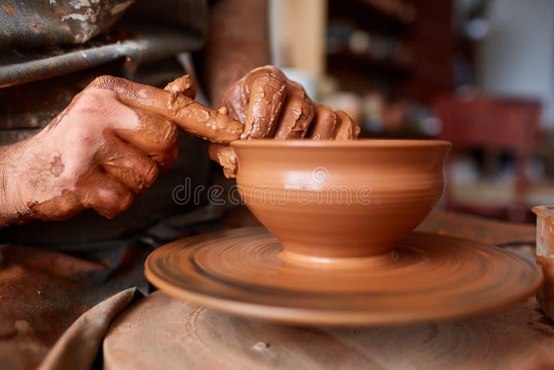 Närbildhänder av en manlig keramiker i förklädeformer bowlar från lera, selektiv fokus arkivfoto