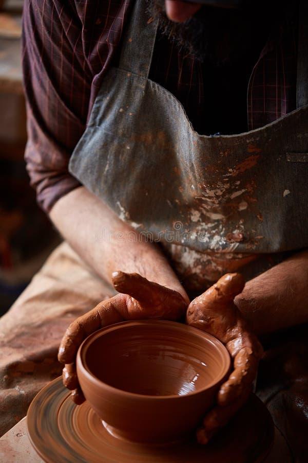 Närbildhänder av en manlig keramiker i förklädeformer bowlar från lera, selektiv fokus arkivbild