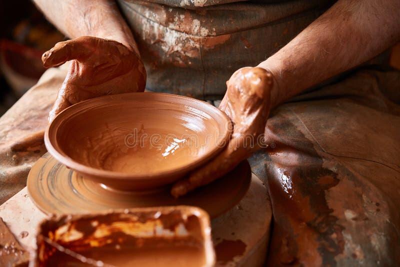 Närbildhänder av en manlig keramiker i förklädeformer bowlar från lera, selektiv fokus arkivbilder