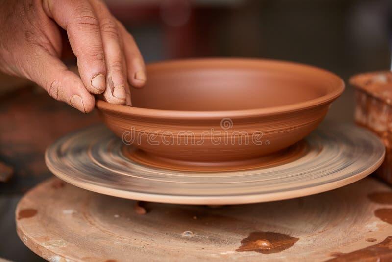 Närbildhänder av en manlig keramiker i förklädeformer bowlar från lera, selektiv fokus arkivfoton