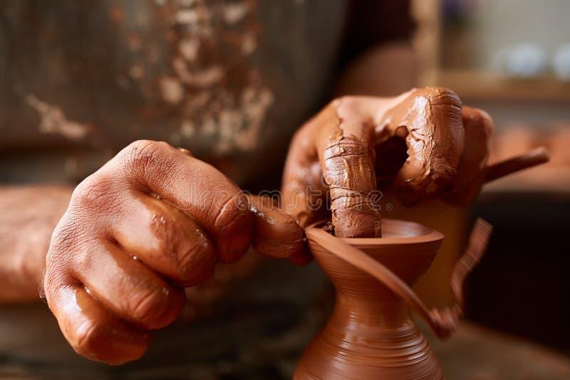 Närbildhänder av en manlig keramiker i förklädet som gör en vas från lera, selektiv fokus arkivbild
