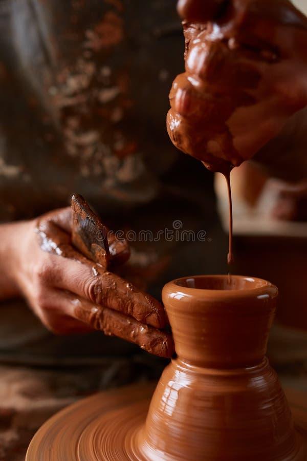 Närbildhänder av en manlig keramiker i förklädet som gör en vas från lera, selektiv fokus royaltyfri bild