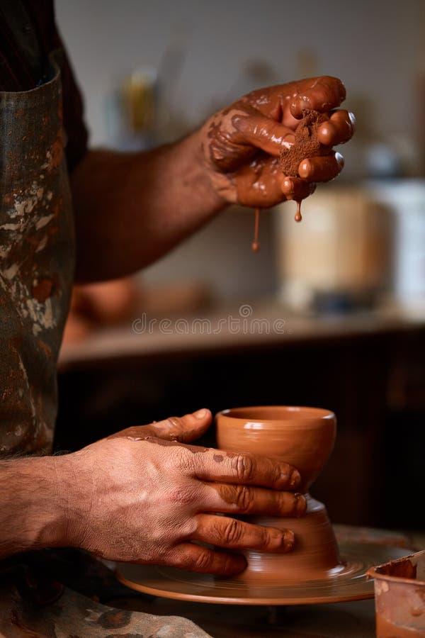 Närbildhänder av en manlig keramiker i förklädet som gör en vas från lera, selektiv fokus royaltyfria bilder